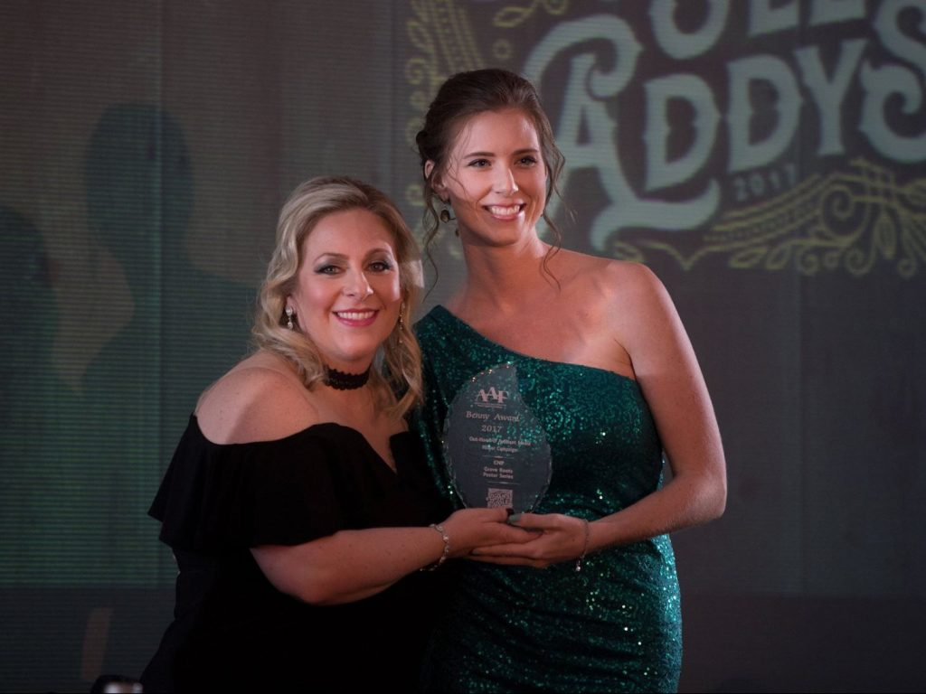 Illustrator Shannon Viox accepts the Benny Award for the Grove Roots Brand material